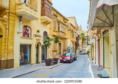 VICTORIA, MALTA - JUNE 15, 2018: Walk the quiet shopping street with many stores, located in old edifices, on June 15 in Victoria.