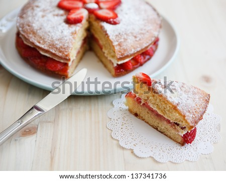 Victoria sponge cake with strawberries, jam and whipped cream with a cut out piece and a knife on a wooden table