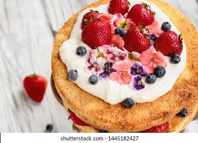 Victoria Sponge Cake with whipped cream, sugared flowers, strawberries and blueberries over a white wooden rustic table top. Image shot for above with blurred background..