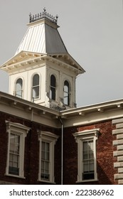 Victorian cupola with iron-railed 'widows walk' and windows atop corner of red brick 1882 building/Mansard-roofed Cupola with 'Widows Walk' near Red Brick Corner of Old Building'/Victorian building