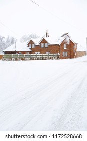 A Victorian farmhouse in winter with snow covered road in the foreground. England, UK