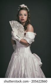 Victorian fashion woman wearing white dress. Holding fan. Studio shot against grey.