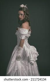 Victorian fashion woman wearing white dress. Studio shot against grey.