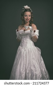 Victorian fashion woman wearing white dress. Holding porcelain tea cup. Studio shot.