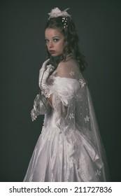 Victorian fashion woman wearing white dress. Holding handbag. Studio shot against grey.