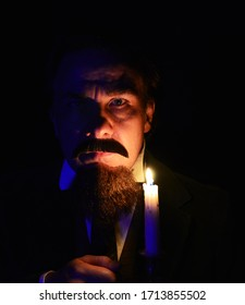 A Victorian gentleman  holding a candle