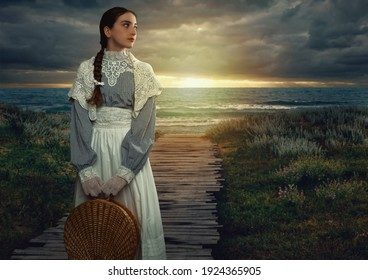 Victorian girl with a hood and a wicker basket in her hands dressed in a white dress and blue striped blouse stands on the seashore at sunset.
