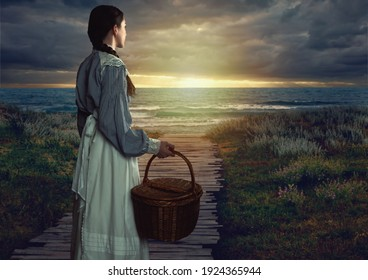 Victorian girl with a wicker basket in white dress and blue striped blouse at seaside at sunset.