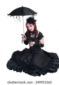 Victorian Goth girl, wearing a black dress, seated on ground, holding parasol and a glass of wine/