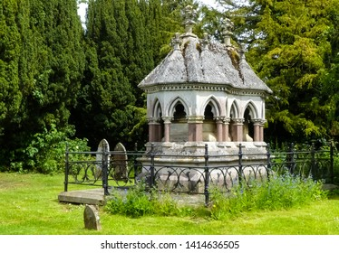 Victorian Gothic Revival mausoleum protected by black wrought iron railings in a natural setting of a rural village churchyard. Northamptonshire. England.
