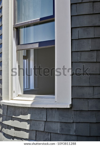 Victorian home under renovation with wood shingles and old wood framed window