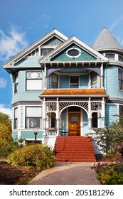 Victorian house in teal blue colors. Front door and steps