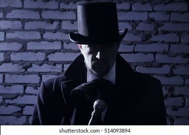 Victorian man in the black coat, top hat and in a tie on a wall background