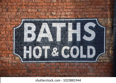 A victorian sign for hot and cold baths painted onto a brick wall