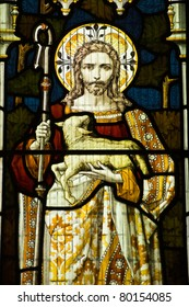 Victorian stained glass window showing Jesus Christ and the lamb of God.