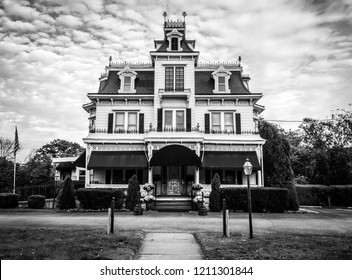 Victorian style funeral home is meticulously maintained and ornate with unique crow's nest in Port Jervis, NY, black and white