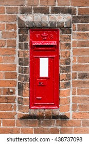 Victorian traditional red postbox set within an old brick wall.