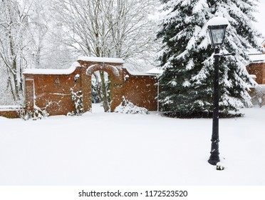 A Victorian walled garden and brick archway covered in snow in winter