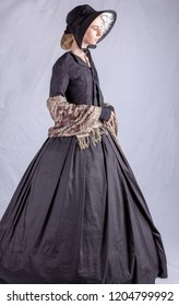 Victorian woman in black ensemble on plain backdrop