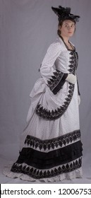 Victorian woman in black and white bustle dress