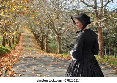 Victorian woman on autumn road with bonnet back view