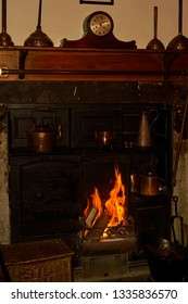 A Victorian wood-burning cast-iron range with lit log burning fireplace and oven, mantle and copper utensils
