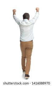 Victorious casual man walking forward celebrating with his hands up in the air while wearing a white shirt and brown pants on white studio background