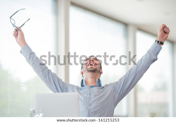 Victorious corporate man celebrating with his arms lifted in the air