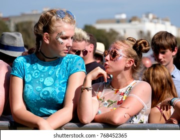 Victorious Festival - 26th August, 2017: Two teenage girls wearing glitter face paint leaning on a barrier talking face to face at   Victorious Festival, Southsea, Portsmouth Hampshire, 26 August 2017