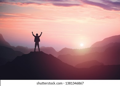 Victorious male person standing on mountain top with arms raised. Winning and success. Achievement and accomplishment in life. Toned image.