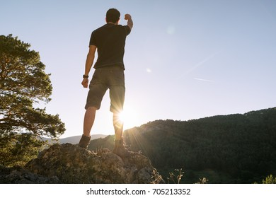 Victorious man on top of the mountain raises his arm from the rays of the sun
