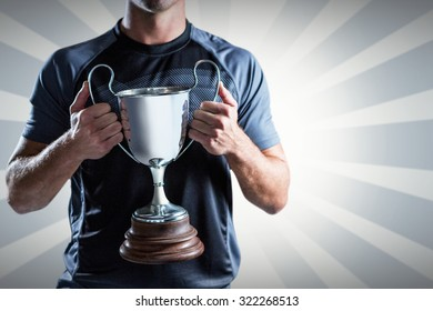 Victorious rugby player holding trophy against linear design