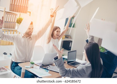 Victory! Cheerful successful businesspartners celebrating breakthrough in their modern sunny workplace throwing documents up