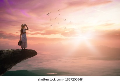 Victory concept: Silhouette traveler woman with birds flying on mountain sunset background