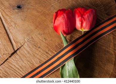 Victory day, St. George ribbon and red tulips on wooden background