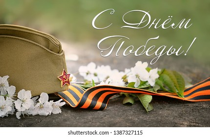 Victory day - text in Russian language. 9 May, George ribbon, flowers and military cap. holiday Victory Day background.  template background celebration of may 9, Victory Day 1945.