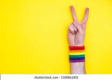 Victory hand gesture with gay pride rainbow flag wristband on a yellow background