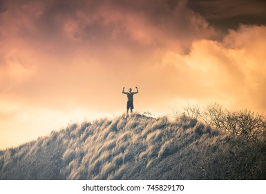 Victory, motivational image, life goals, courage. Man flexing high up on a mountain.