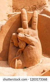 Victory. Peace hand gesture. Two fingers up in the sand