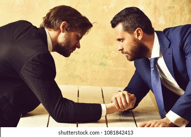 victory and reward, defeat and loss, opposition of businessmen or men in suit, arm wrestling and power, business situation