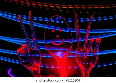 Victory sign represented using plastic forks and spoon - Abstract Light Painting at night - Light Art Photography
