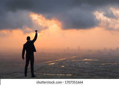 Victory and success concept! Strong confident businessman celebrating on top of skyscraper overlooking against a city sunrise/sunset background.