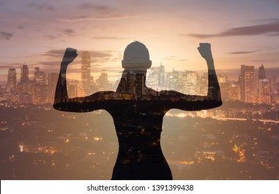 Victory and success! Silhouette strong confident woman flexing against a city skyline background. Double exposure