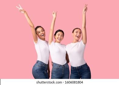 Victory. Three Happy Multiethnic Girls Gesturing V-Sign Having Fun Standing On Pink Background. Studio Shot