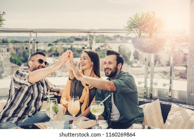 Victory. Two bearded men and beautiful young woman having fun at outdoor cafe. They are slapping palms with raising hands and laughing