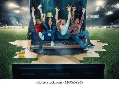 Victory. Win, winners. Happy soccer football fans sitting on sofa at home and watching TV in the middle of a football field. Football concept. Full immersion into the match. Real emotions. Live
