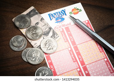 Vidalia, Georgia / USA - May 27, 2019: A close-up shot of the unmarked official printed numbers game form used in buying tickets to Georgia's Fantasy 5 lottery set on wood with pen and US money.