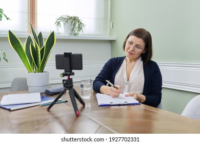 Video blog vlog help of professional psychologist. Mature confident woman counselor recording video stream, online consultation group and individual, female using smartphone on tripod for video chat