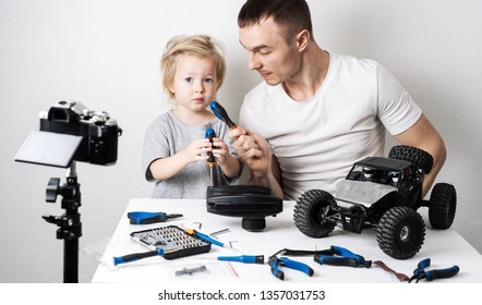 Video blogging: Dad takes a comic interview with a little daughter during the repair of a radio-controlled car buggy model.