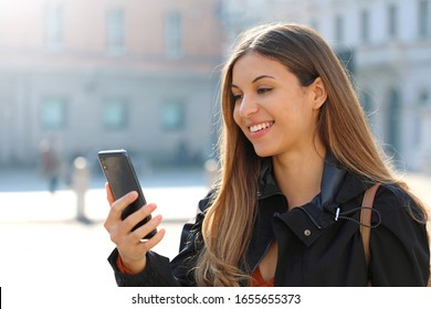 Video Call. Beautiful student girl makes a video call with her smart phone in city street.